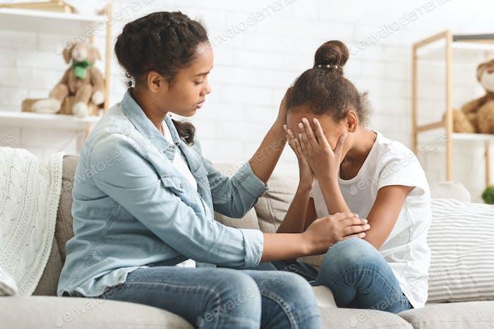 weinend kleines Mädchen wird getröstet durch ihre ältere Schwester