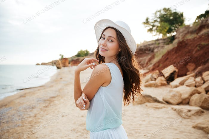 Happy young woman in white hat waalking near the sea