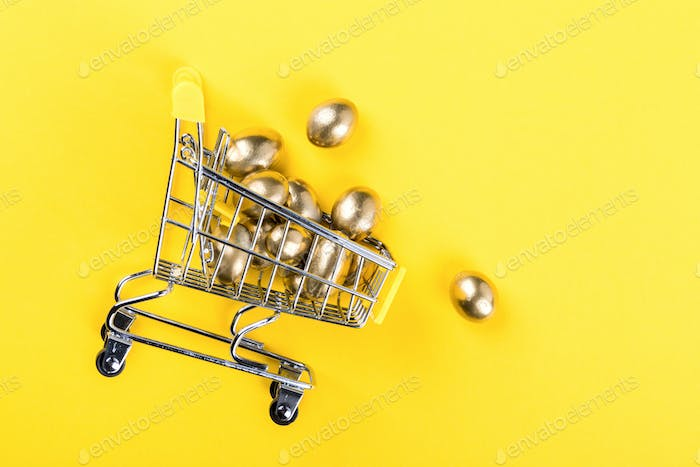 Easter composition.Shopping cart trolley on a bright yellow background