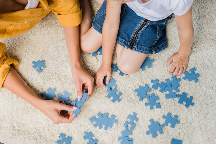 cropped top view shot of mother and daughter assembling blank puzzle