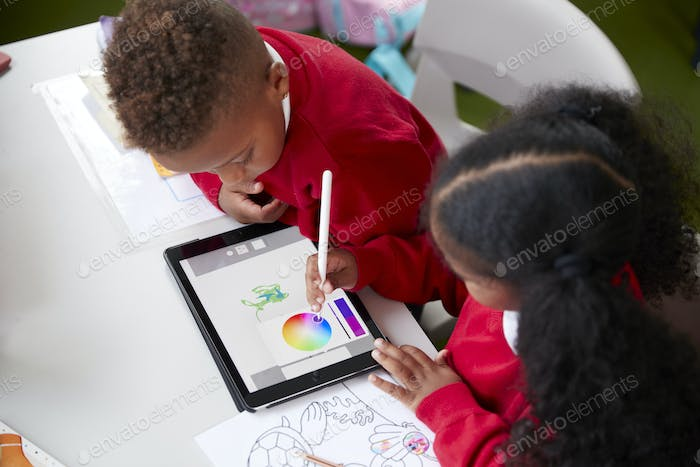 Two kindergarten school kids sitting at a desk in a classroom drawing with a tablet computer