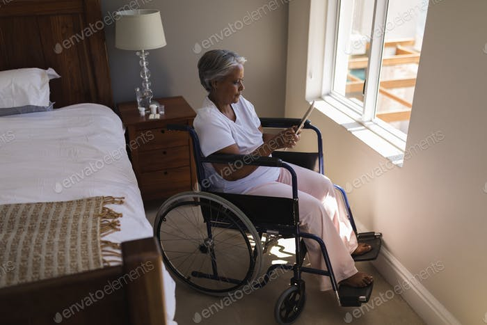 Side view of a disabled senior African American woman using digital tablet in bedroom at home