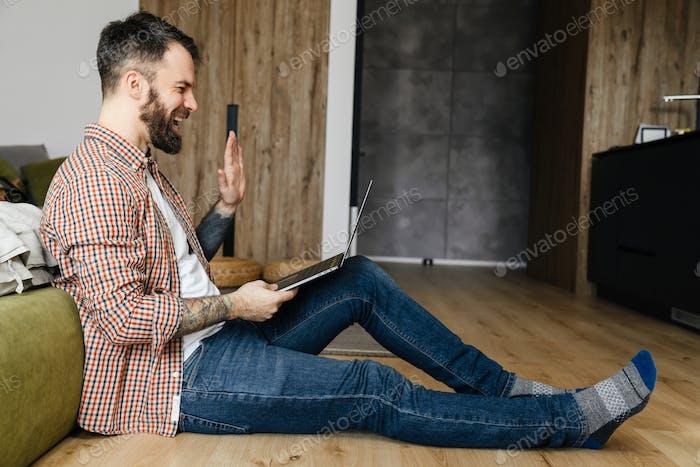 Happy mid aged brunette bearded man working