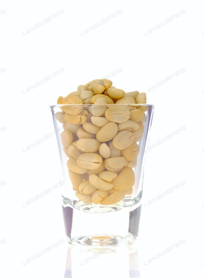 Rohe Kaffeebohnen in Glas auf weißem Hintergrund.