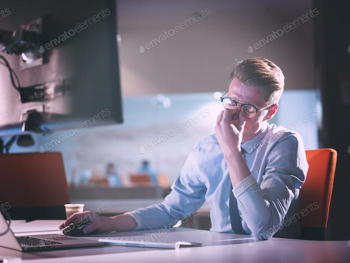 man working on computer in dark office