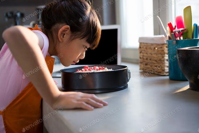 Mädchen Blick auf Kuchen in Behälter