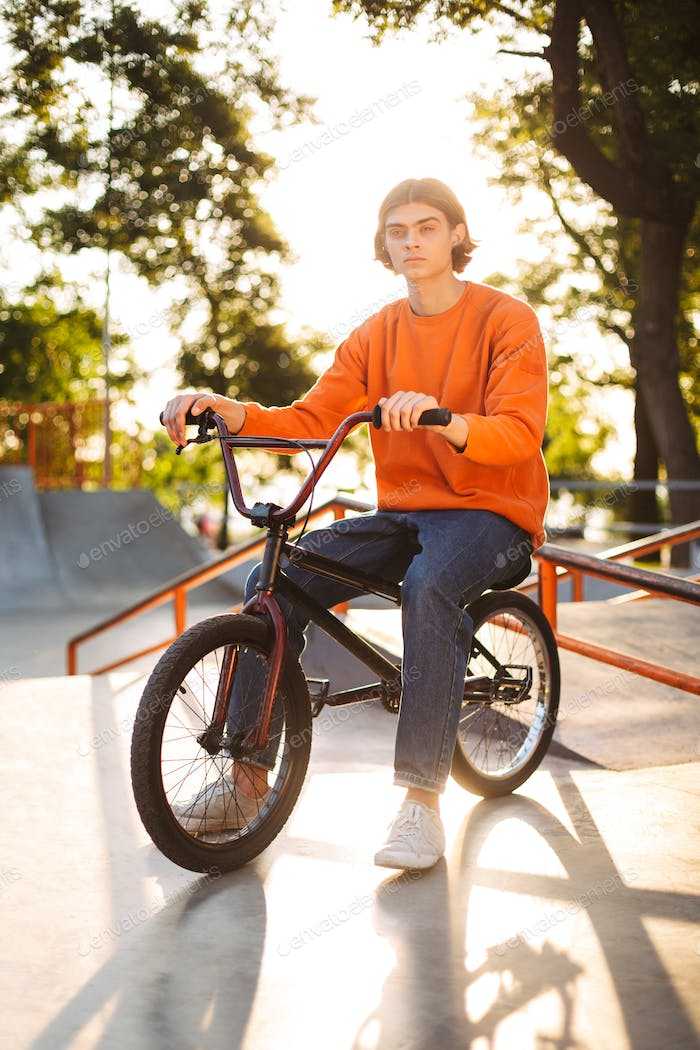 Young man in orange pullover and jeans sitting on bicycle though