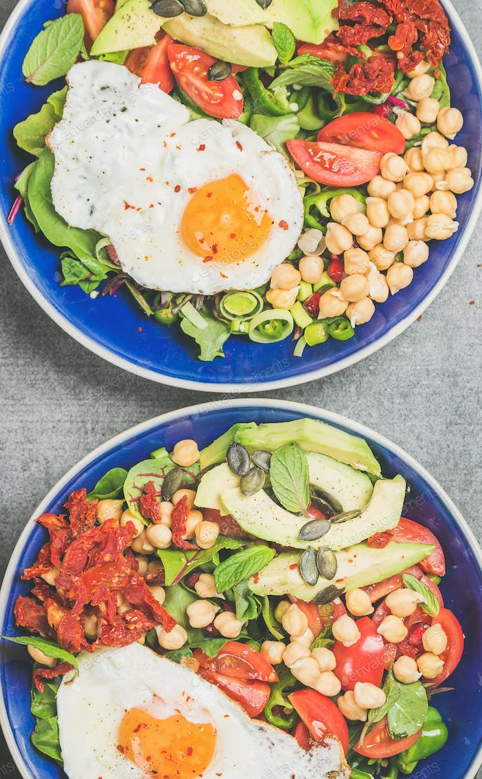 Close-up of breakfast with fried egg, chickpea, vegetables, seeds, greens