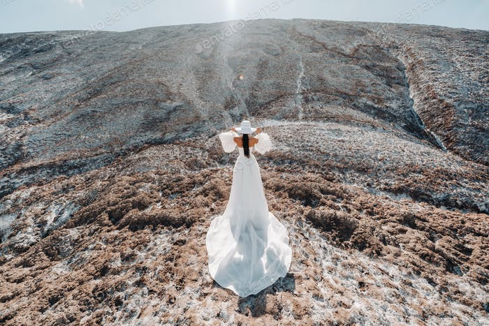 Beautiful unrecognizable bride in a wedding dress and hat on top of the salt mountains. Stunning
