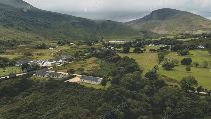 Scottish village cottages, houses at road aerial. Whiskey distillery at mountain. Nature landscape