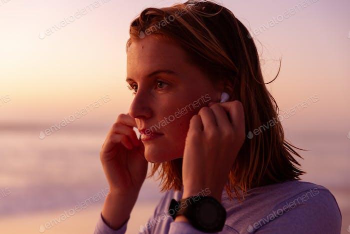 Beautiful woman wearing earphones on the beach