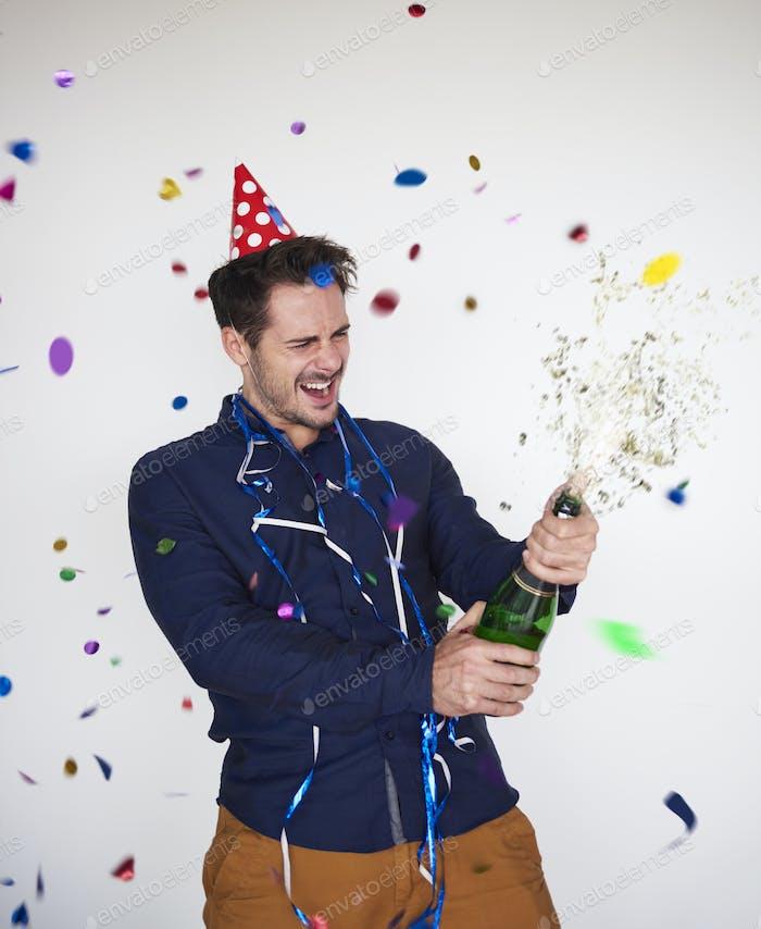 Mann öffnet eine Flasche Champagner