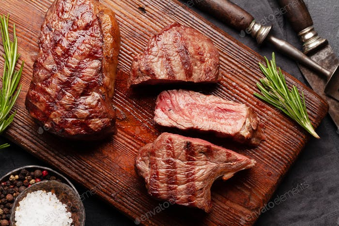 Grilled beef steaks on cutting board