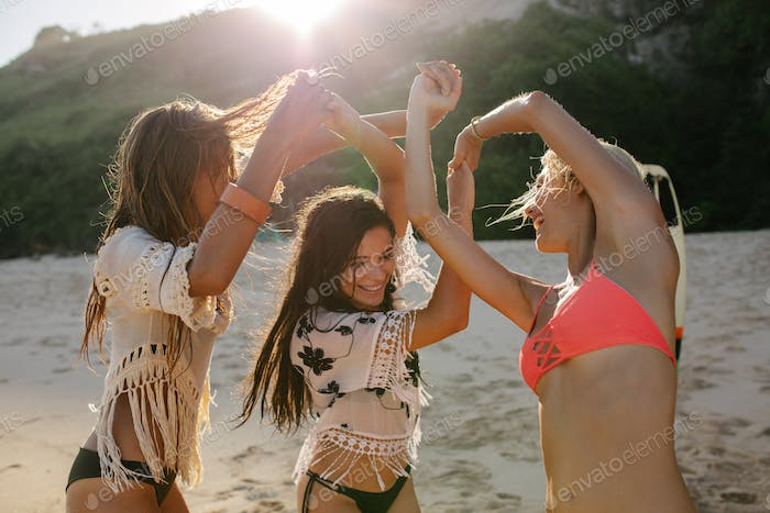 Female friends dancing on the beach and having fun