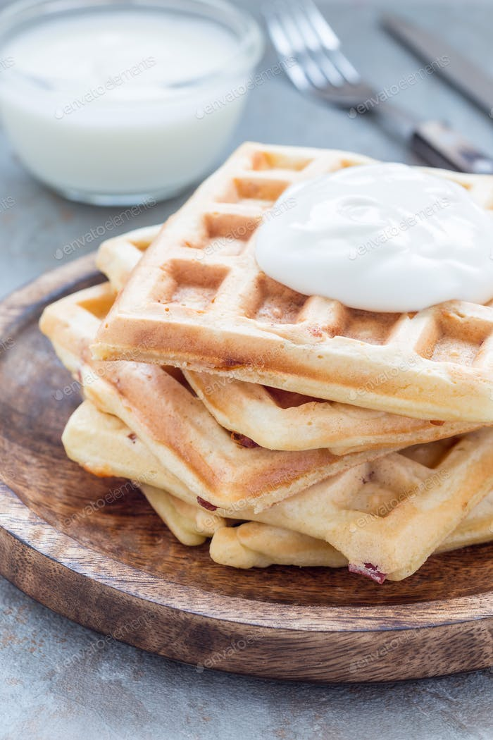 Savory belgian waffles with bacon and shredded cheese on wooden plate, vertical