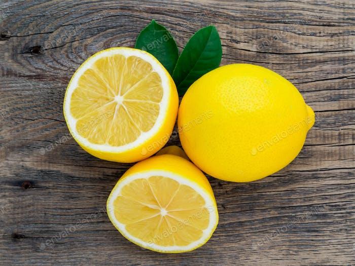 свежий лимон и отрезать половину на деревянном старом столе, вид сверху