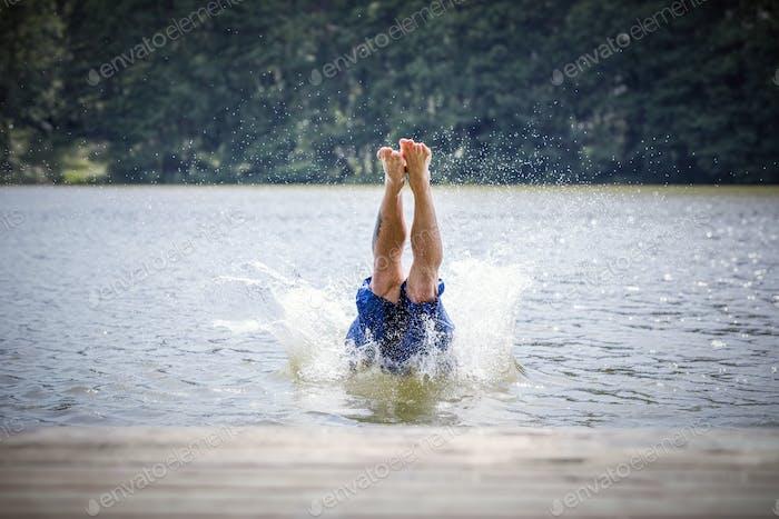 Ein junger Mann, der in einen See eintaucht.