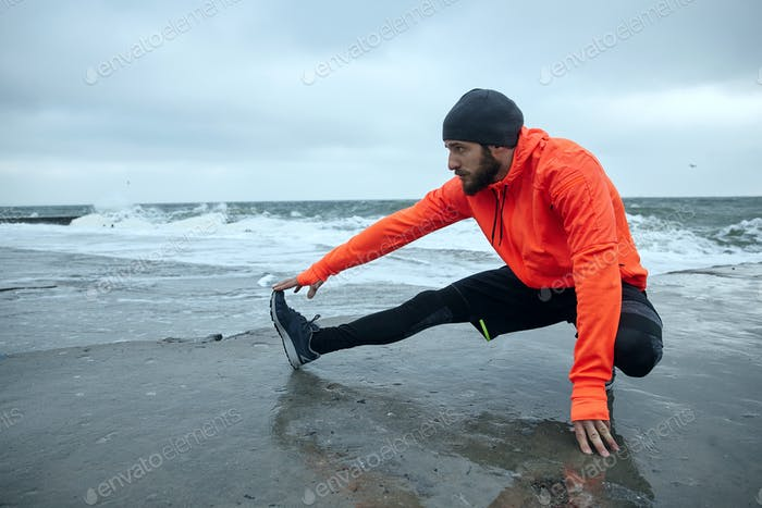 bearded guy doing stretching for legs on coastline of sea, preparing for morning workout