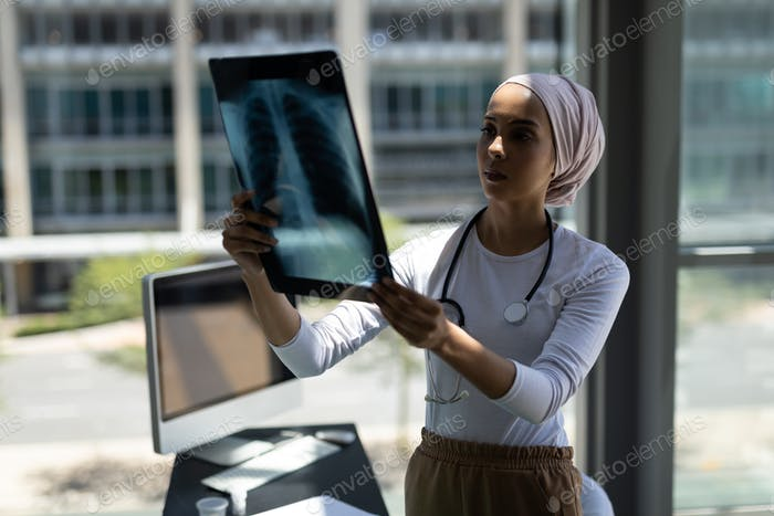 Front view of beautiful young mixed-race female doctor looking at x-ray report in modern hospital