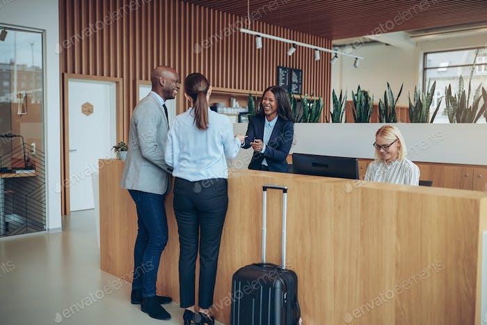 Zwei lächelnde Gäste geben ihre Reservierung Informationen zur Hotelrezeption