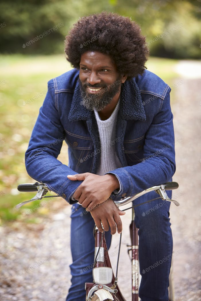 Black middle aged man sitting on a bike in  a park, leaning on the handlebars smiling