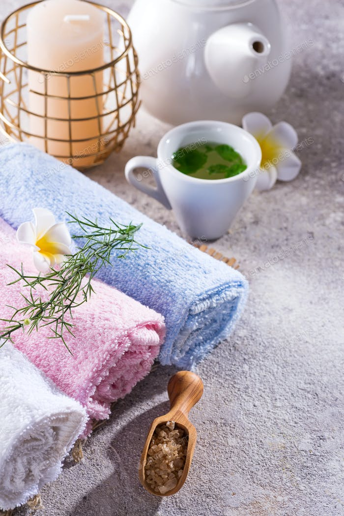Color towels with flower, spoon of salt, on bamboo mat, bath spa treatment and green tea on stone