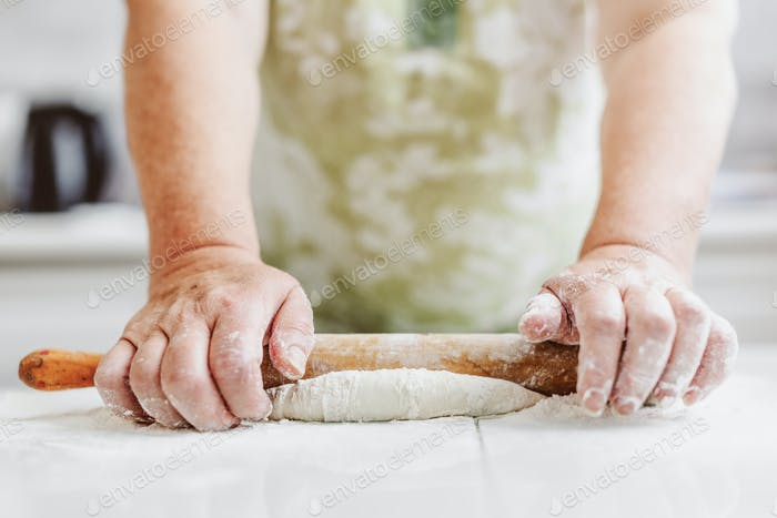Woman kneading dough at home kitchen