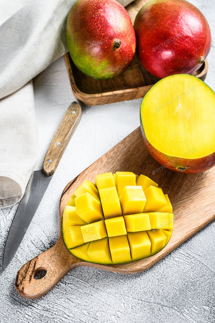 Mango fruit cut into cubes on a cutting Board. Gray background. Top view