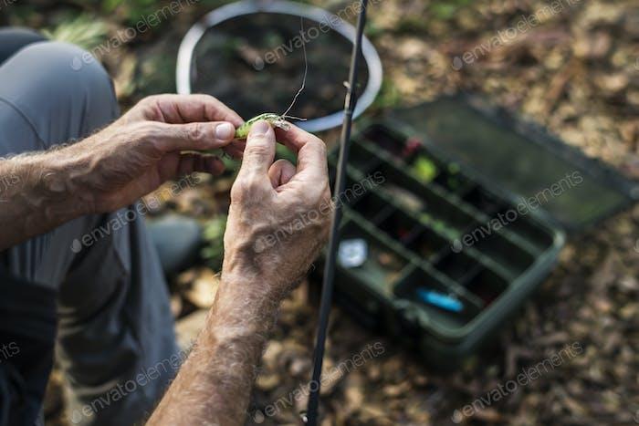 Closeup of a fisherman putting on bait