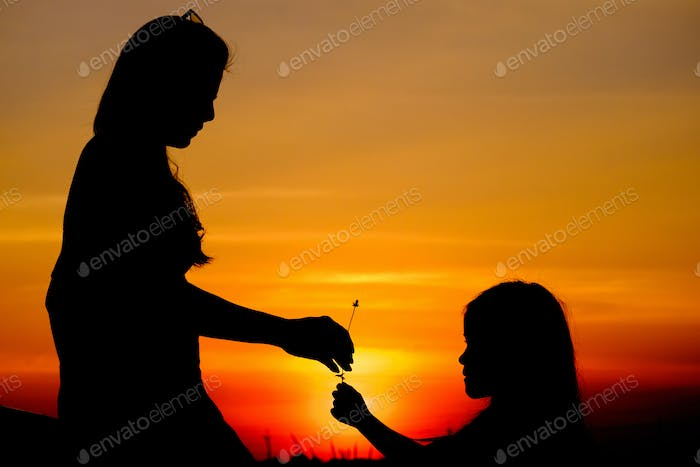 Silhouetted of daughter gives a little flower for mother