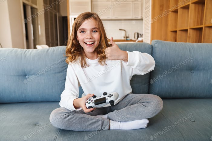 Photo of excited girl showing thumb up and playing video game
