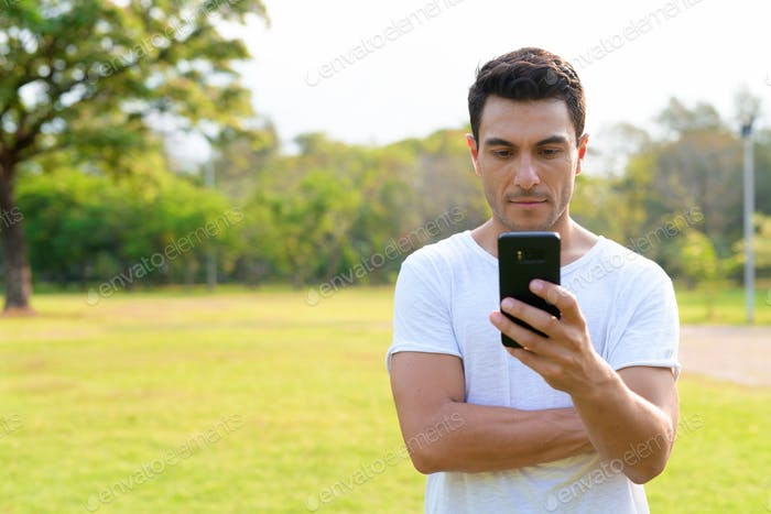 Young handsome Hispanic man using phone at the park