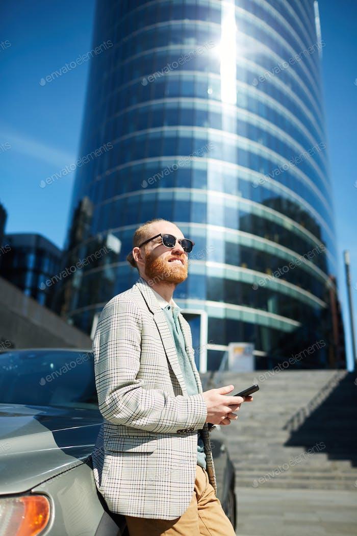 Purposeful entrepreneur leaning on car