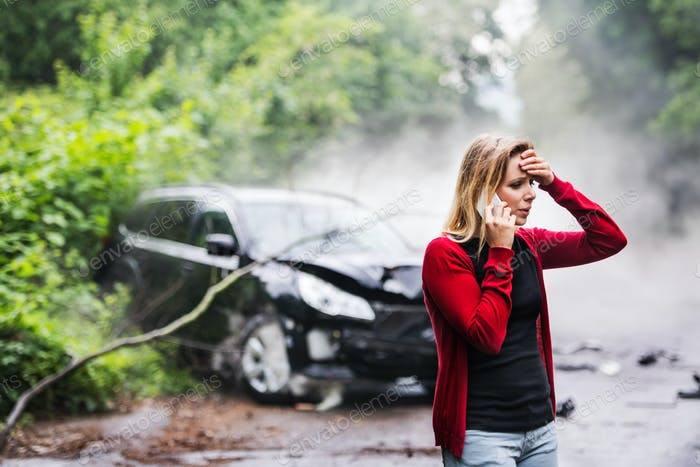 A young woman with smartphone by the damaged car after a car accident, making a phone call.