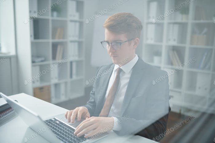 Young confident trader in suit looking through online data