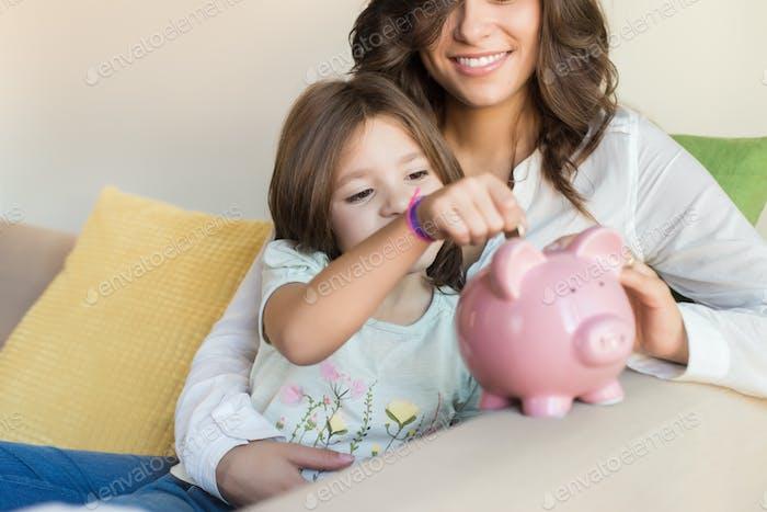 Mutter und Tochter Geld sparen