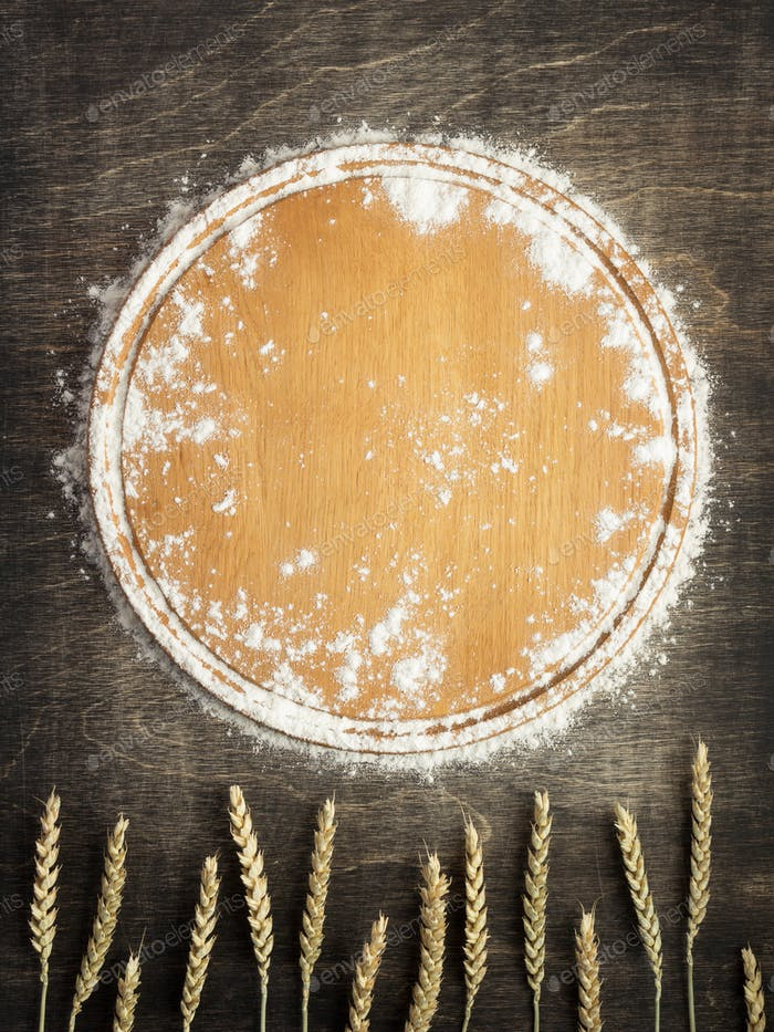 wheat flour and cutting board on wooden background