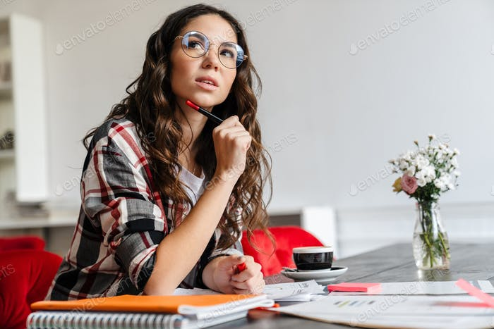 Serious nice woman writing and working with papers