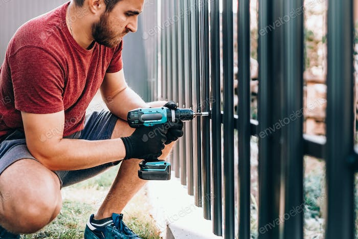worker working with an electric screwdriver on the construction site