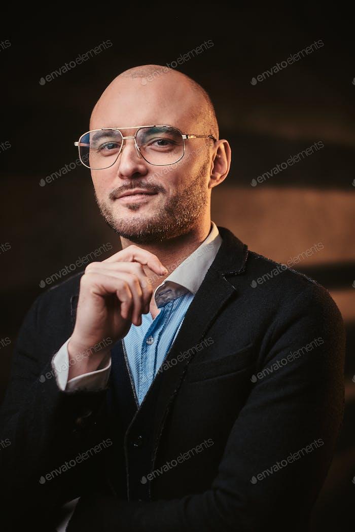 Красивый лысый бизнесмен позирует в темной студии в черной куртке, синей рубашке и очках.