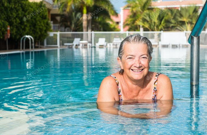 Senior woman, amused, swimming to keep fit in outdoor pool with clear water and sunny day