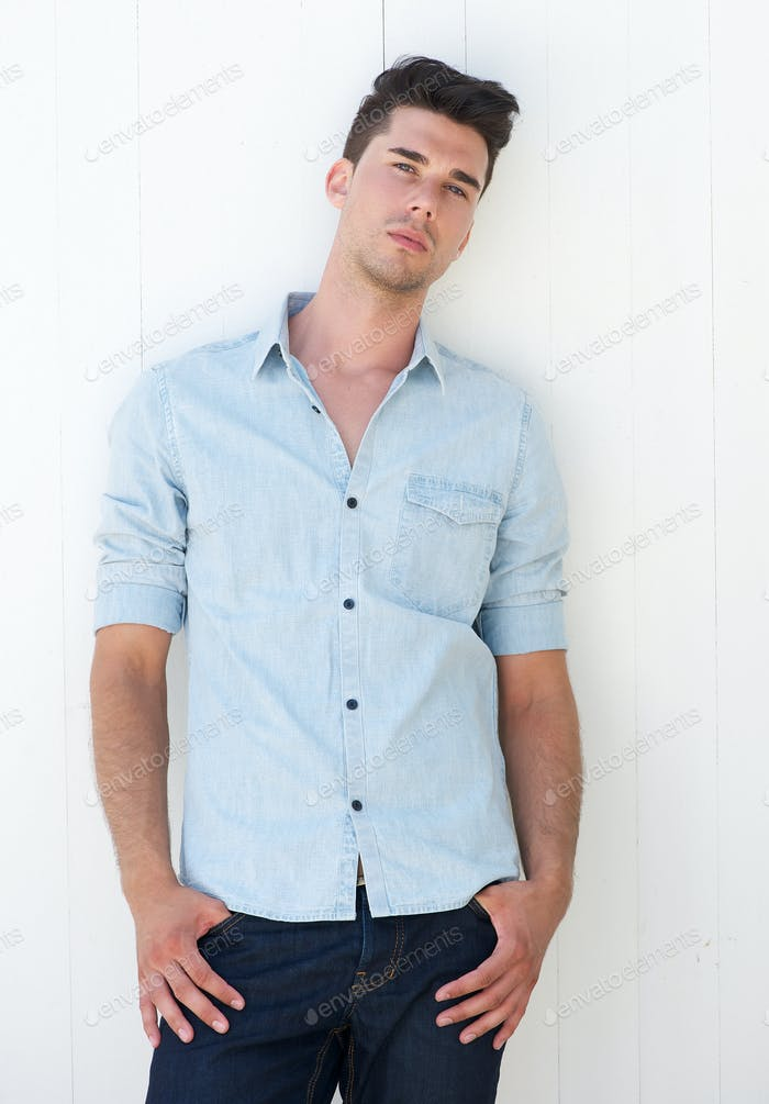 Attractive young man standing outdoors with hands in pocket