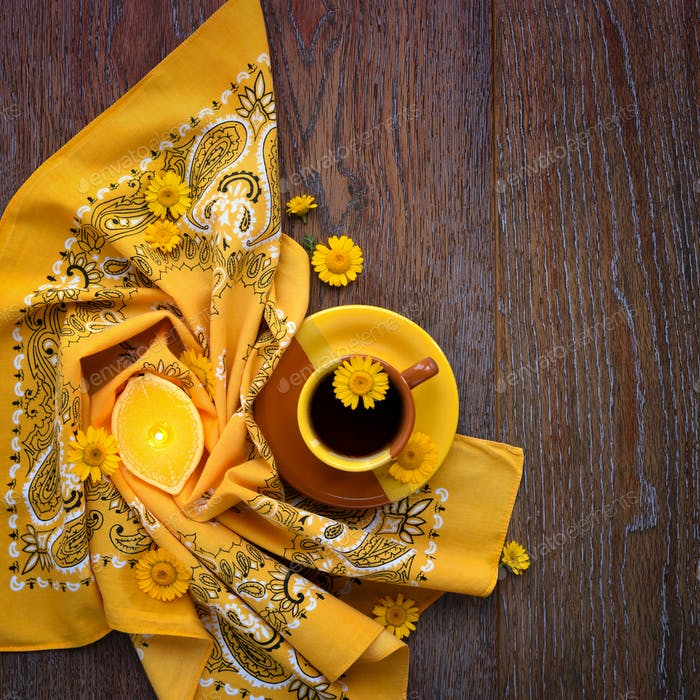 Cup of black tea with yellow daisy flowers on wooden background.