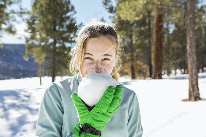 A teenage girl old girl holding and tasting a snowball