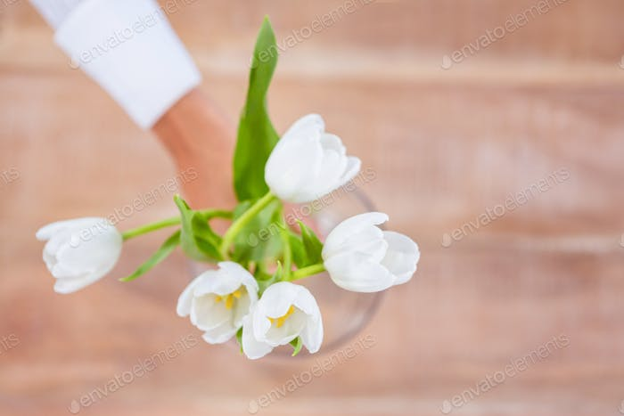 Woman putting a flowers in a vase on desk