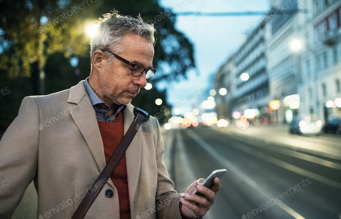 Mature businessman with smartphone standing on a street in the evening.