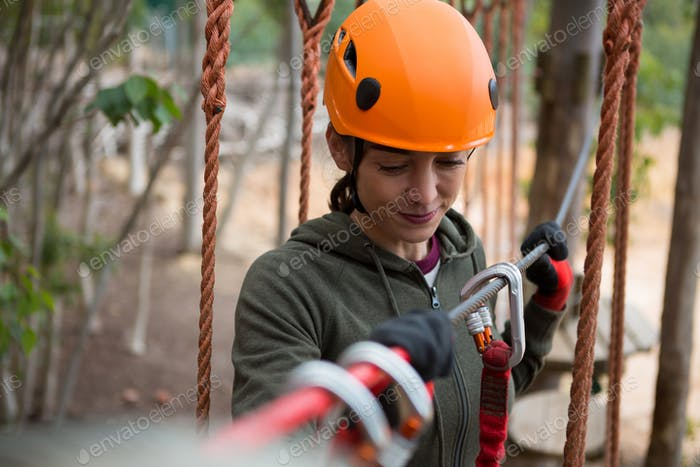 Young smiling woman holding zip line cable in the forest