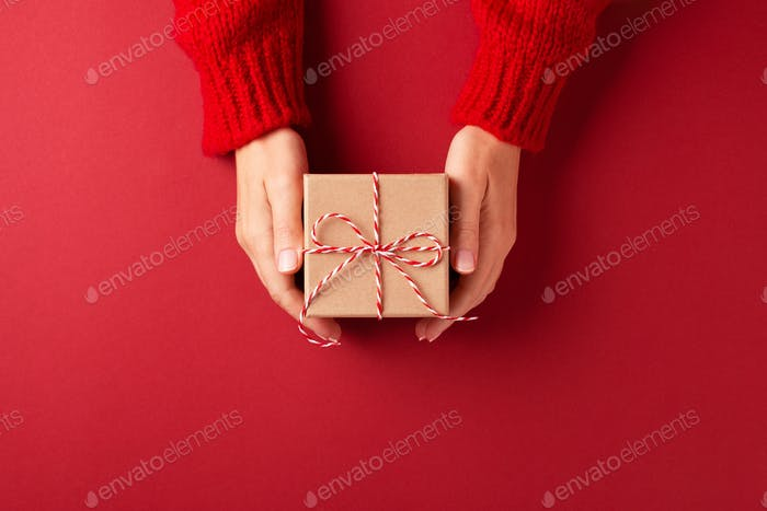 Female`s Hands in Red Pullover Holding Gift Box on Red Background.