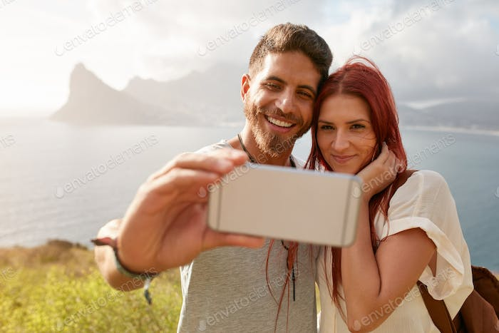 Young couple in nature taking a selfie