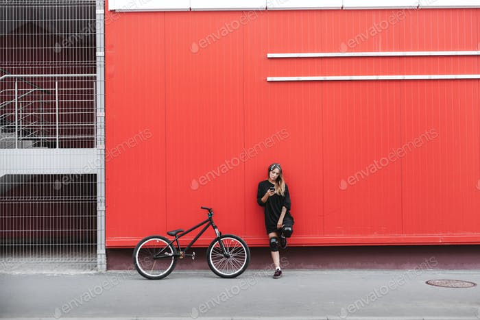 Girl in hockey jersey style with street bicycle